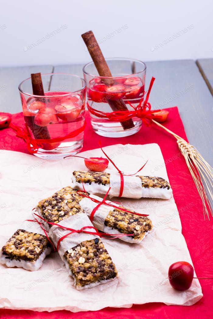 Diet muesli bars with detox apple cinnamon water on red pepper and wooden background.