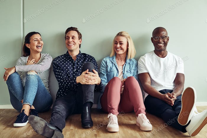 Diverse group of laughing businesspeople sitting on an office floor