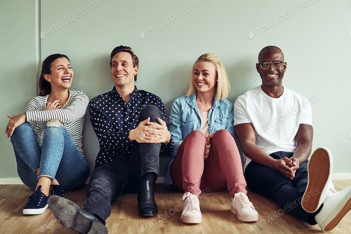 Разнообразная группа смеяных бизнесменов, сидящих на офисном этаже