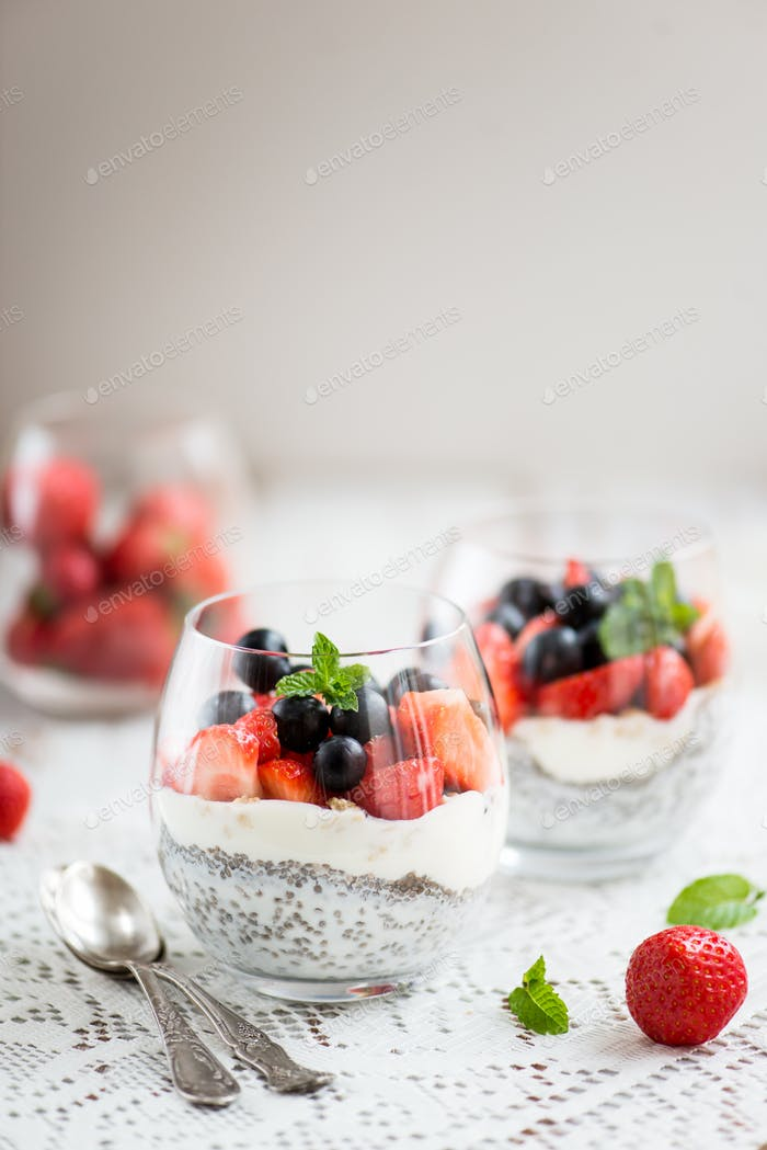 chia seeds in yogurt with granola, yogurt and strawberries, blueberries and mint