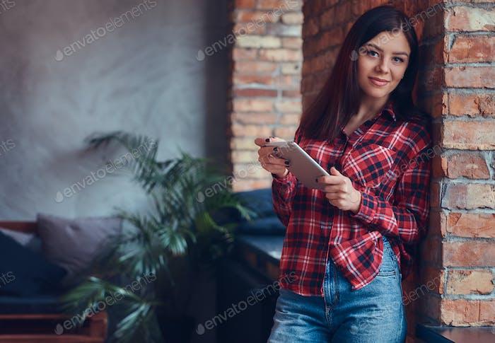 Портрет очаровательной брюнетки в фланелевой рубашке и джинсах остроумие