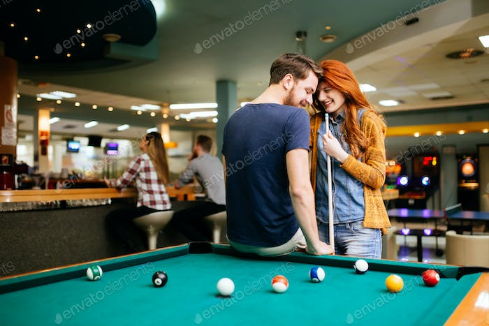 Beautiful couple playing billiards