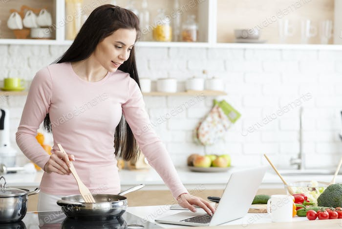 Millennial woman in kitchen cooking with reference the laptop