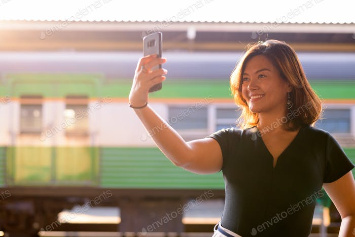 Young happy Asian tourist woman taking selfie at the railway station