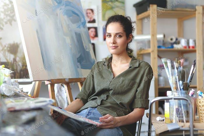Kunst, Arbeit, Inspiration und Kreativität. Porträt einer schönen talentierten jungen Brünetten Künstlerin in