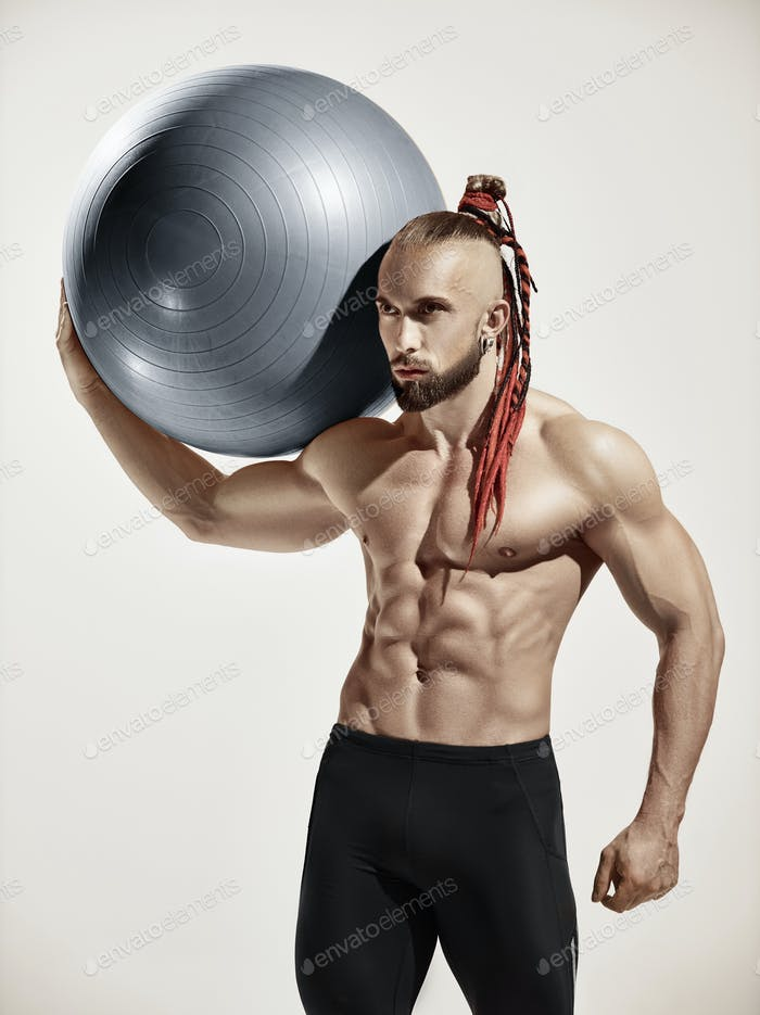 Muscular man holding fitness ball, standing isolated on white