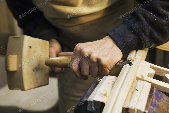carpenter with large mallet and chisel