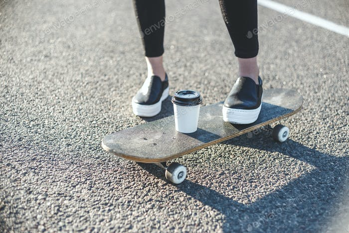 sunrise skateboarding woman legs and coffee on the board