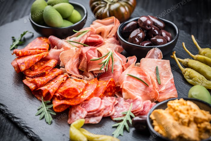Platter of antipasti with a mixture of salami, prosciutto, chorizo, peppers, tomatoes and olives
