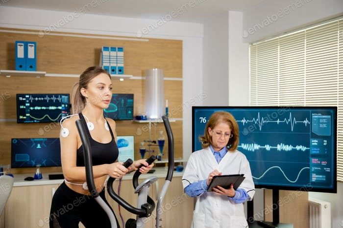 Female athlete testing the stepper with electrodes on her and the doctor making notes in the tablet