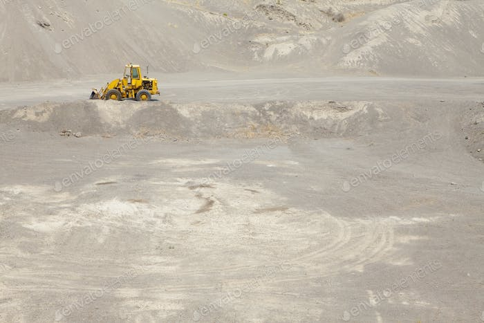 Tractor in a gravel pit. Heaps of gravel and stones. Mining  and quarrying area.