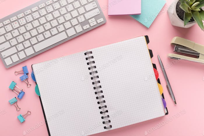 Spiral notepad on pink background, top view