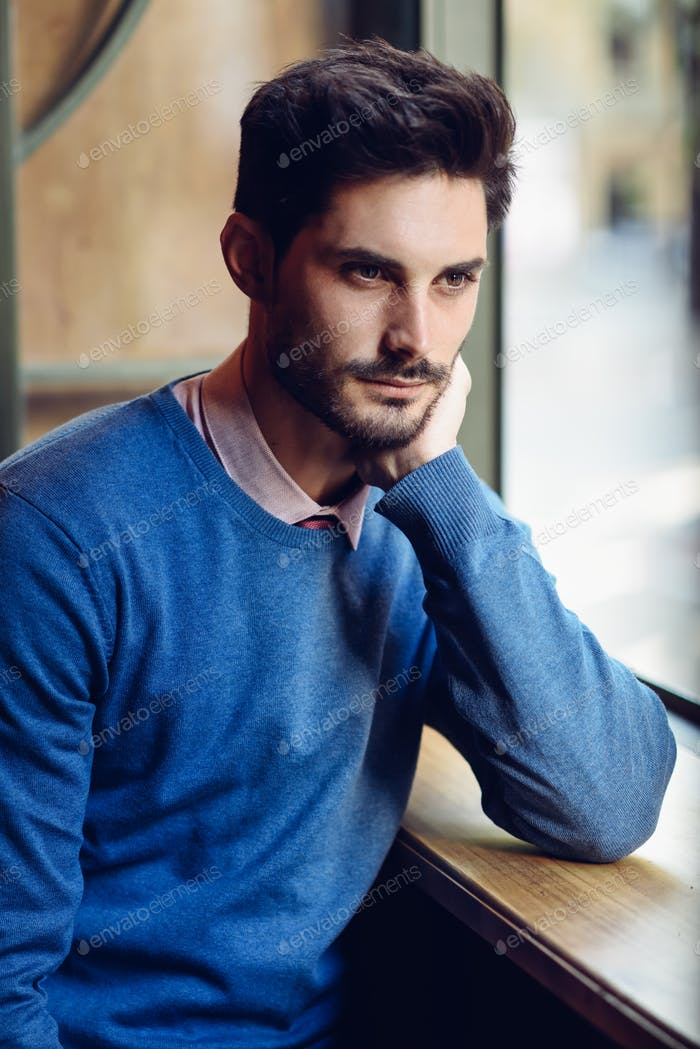 Pensive man with blue sweater with lost look near a window