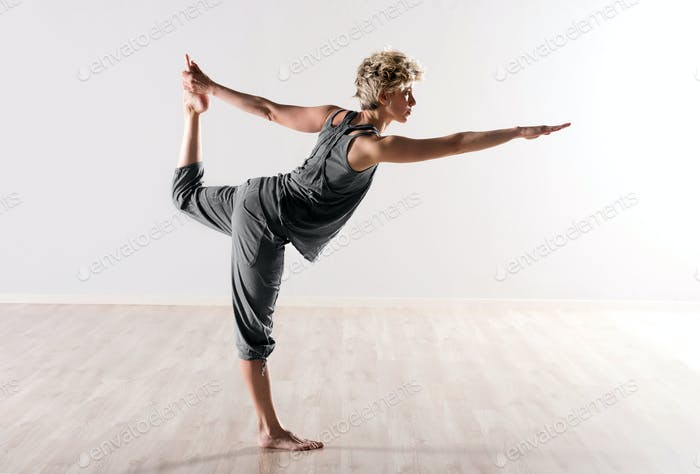 Young woman doing yoga balancing exercises