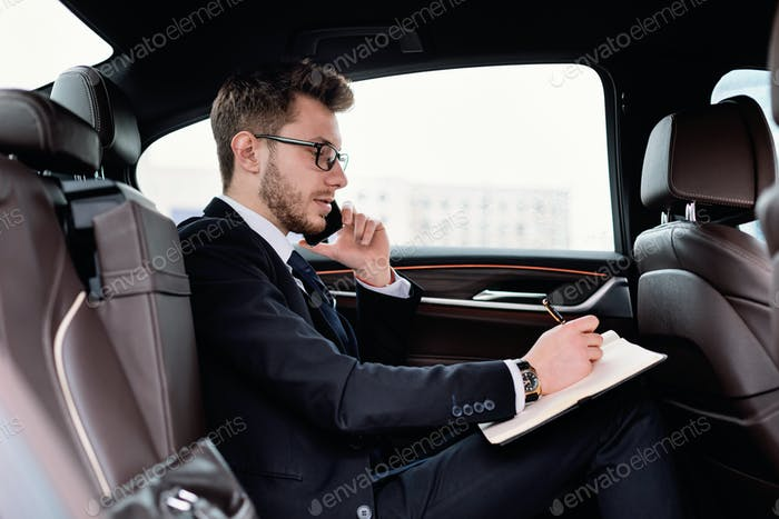 Businessman writing in notebook in luxury car