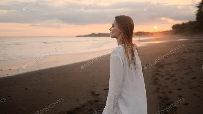 Beautiful romantic girl meeting sunset by the ocean on island