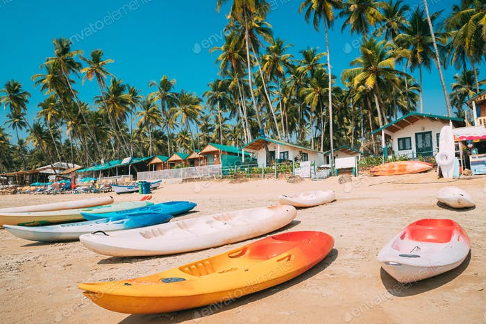 Canacona, Goa, India. Canoe Kayak For Rent Parked On Famous Palolem Beach On Background Tall Palm
