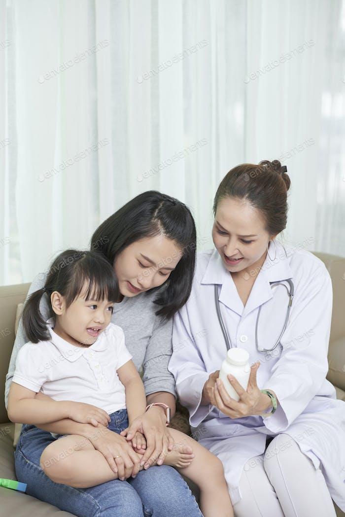 Doctor prescribing vitamins to child