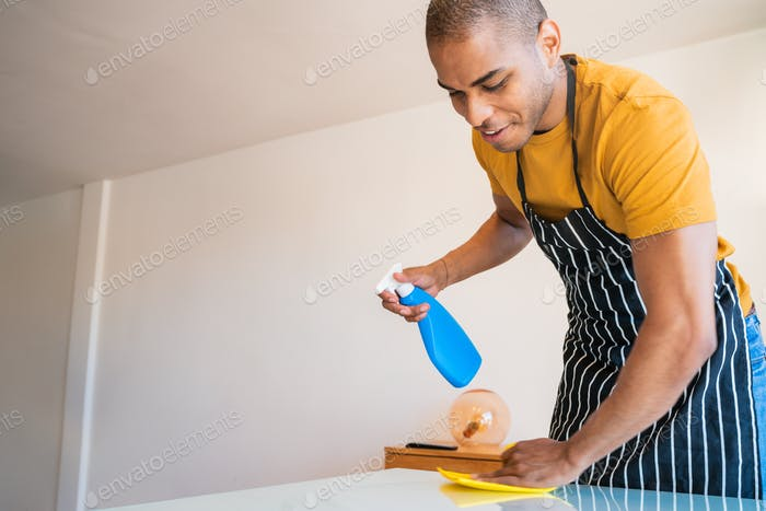 Young latin man cleaning at home.