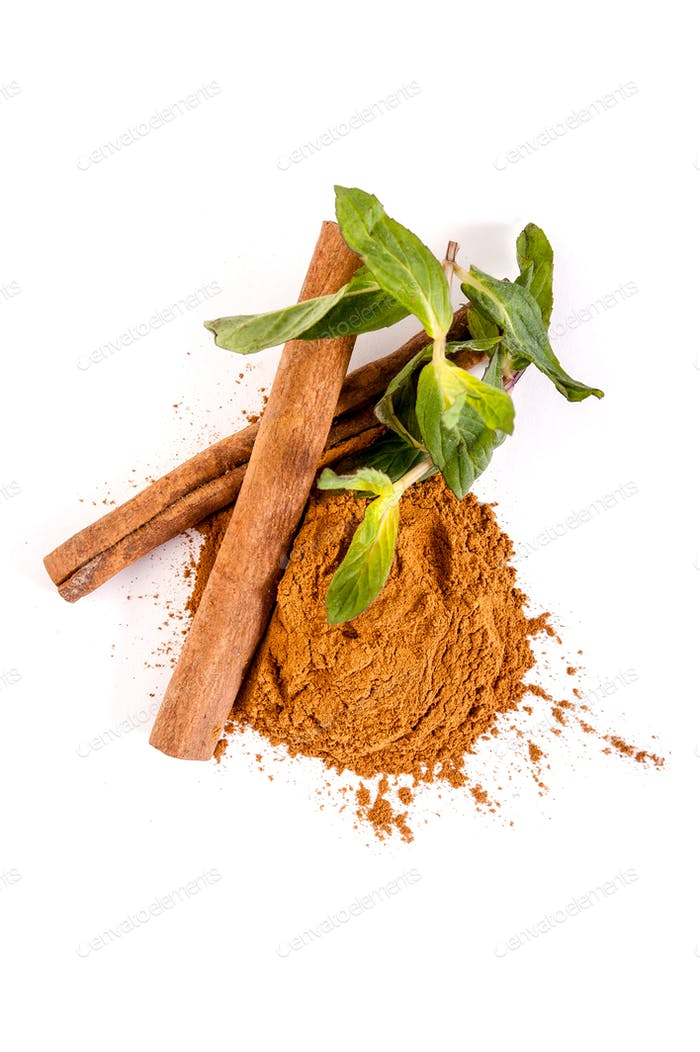 Whole and ground cinnamon and mint leaves on a white background.