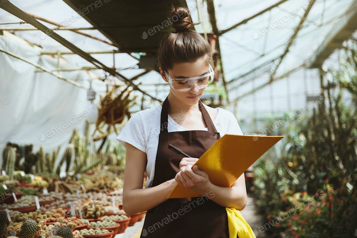Serious young woman standing in greenhouse holding clipboard