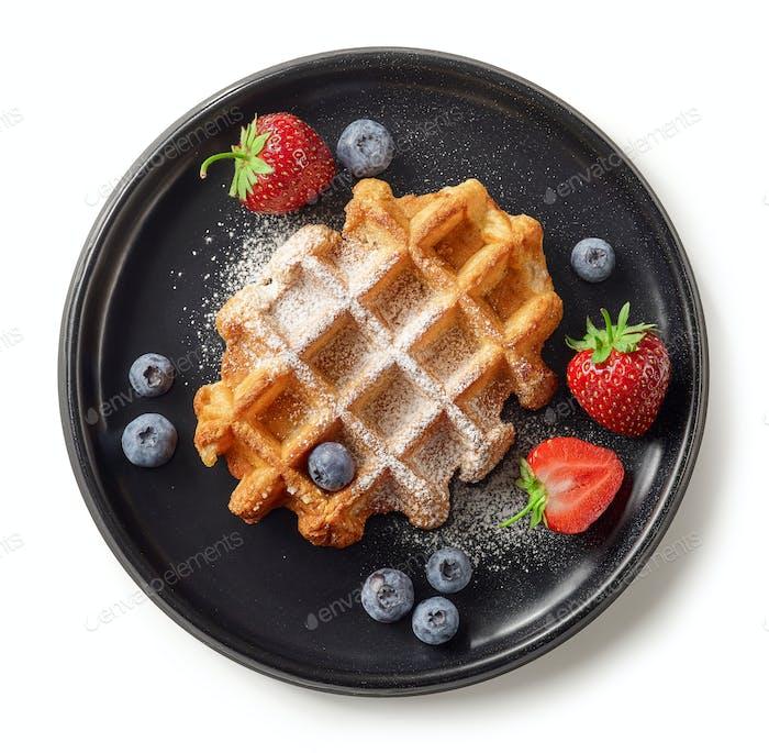 freshly baked belgian waffle on black plate