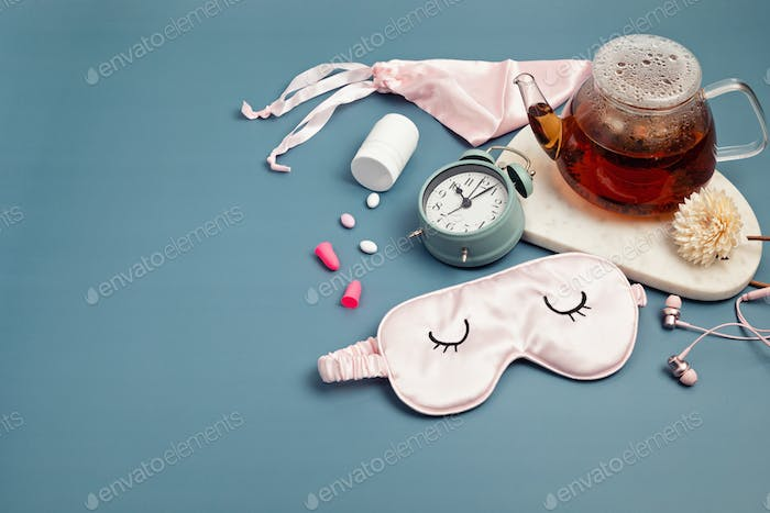Classic alarm clock, sleeping mask, pills and herbal tea. Minimal concept of rest, quality of sleep