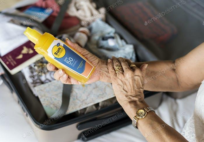 Senior woman applying sunscreen on her arm