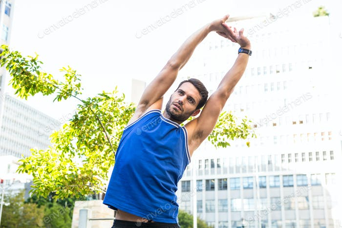 Handsome athlete stretching in the city