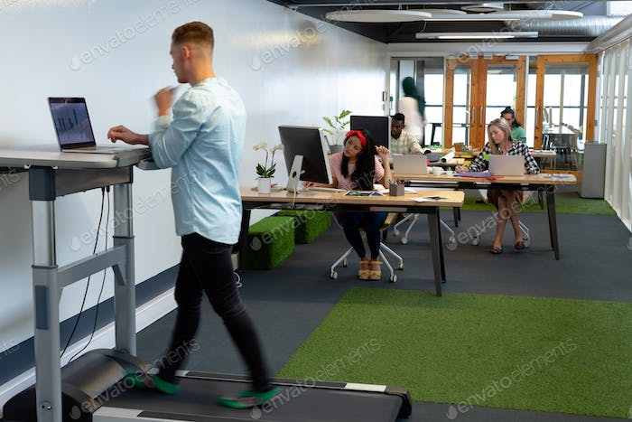 Caucasian businessman working on laptop while exercising on treadmill