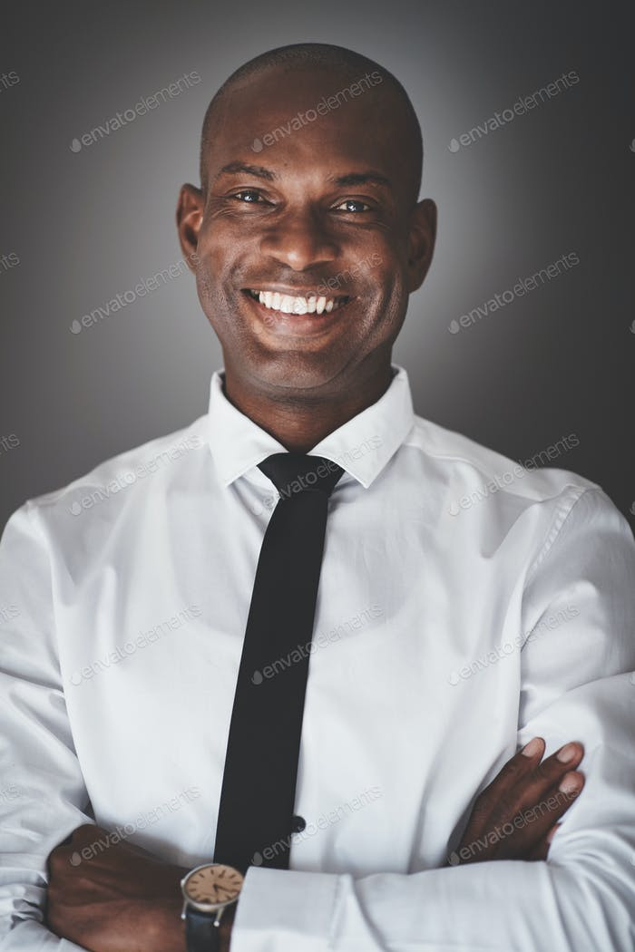 Smiling young African businessman standing against a gray background