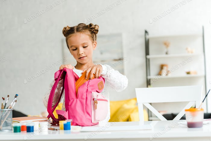 cute schoolgirl putting lunch box in pink backpack