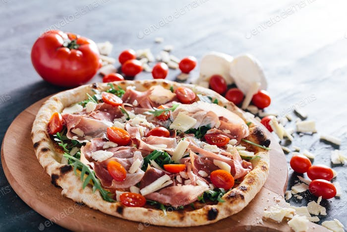 Pizza with ham, cheese, tomatoes and rocket salad .