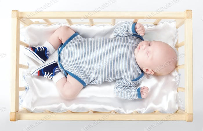 cute newborn baby in wooden bed