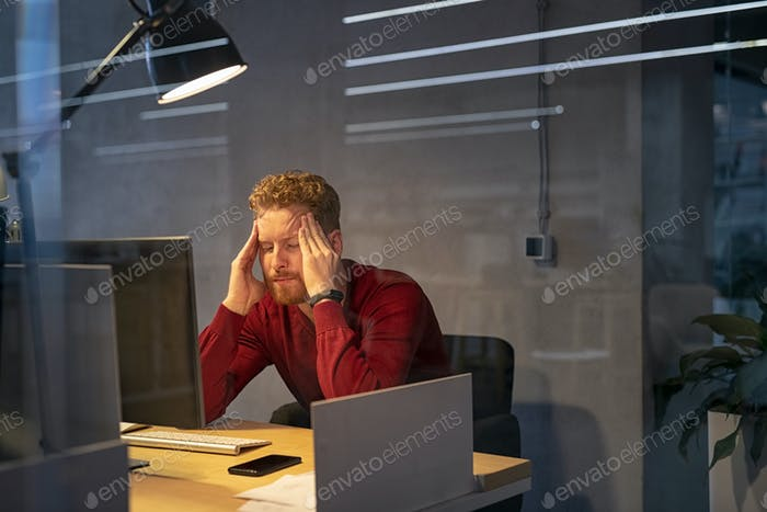 Tired businessman in office working late