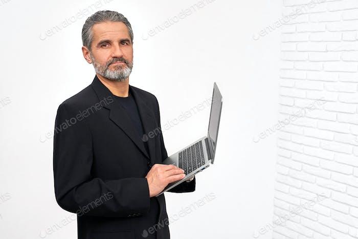 Бородатый человек в черном наряде держит ноутбук