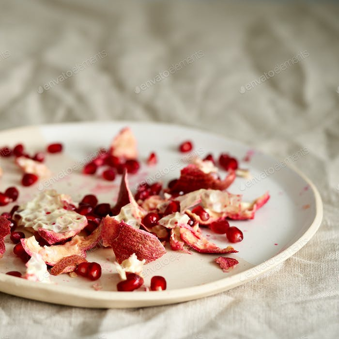 food waste of pomegranate cleaning and seeds on plate on table covered with crumpled beige