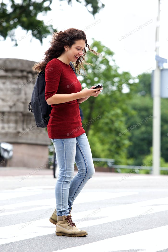 Young urban woman crossing the street with cellphone