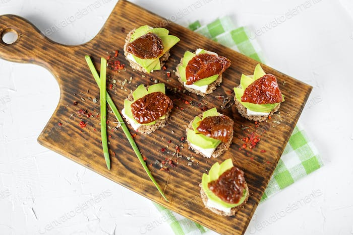 Appetizers with cheese, avocado and dried tomatoes on the board. Concept for food, healthy food