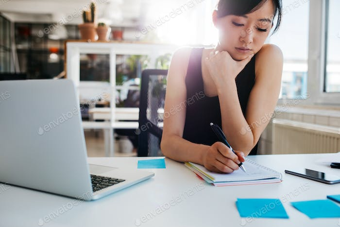 Asian businesswoman writing notes on notepad