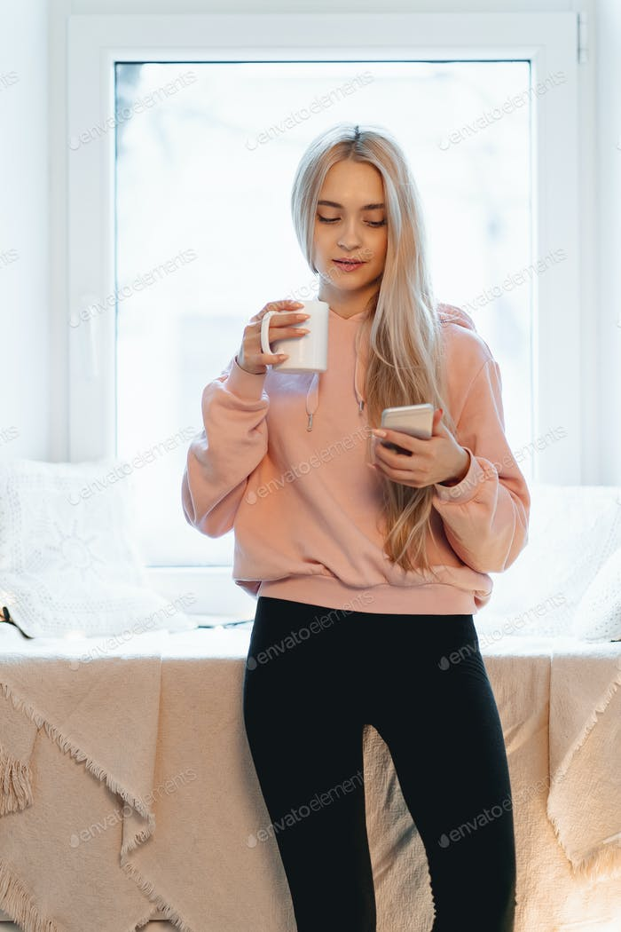 Pretty young woman enjoying coffee while using a smartphone by the windows indoors