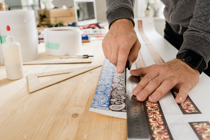 Hands of young craftsman or designer curring ornamented paper by table