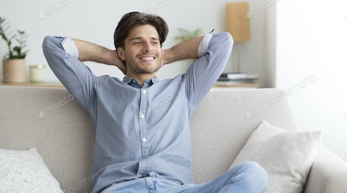 Happy Guy Sitting On Couch Having Lazy Day At Home