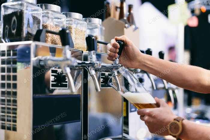 Bartender pouring craft beer from a tap at beerfest