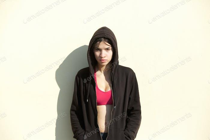 Junge Sportfrau stehend im Freien mit schwarzem Sweatshirt