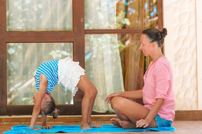 Mother and daughter doing yoga exercise outdoors