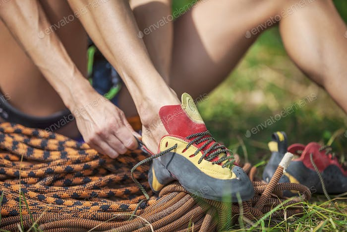 Close up of rock climber putting on climbing shoes while sitting on grass