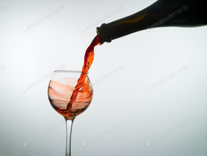Red wine pouring into a wine glass, white background