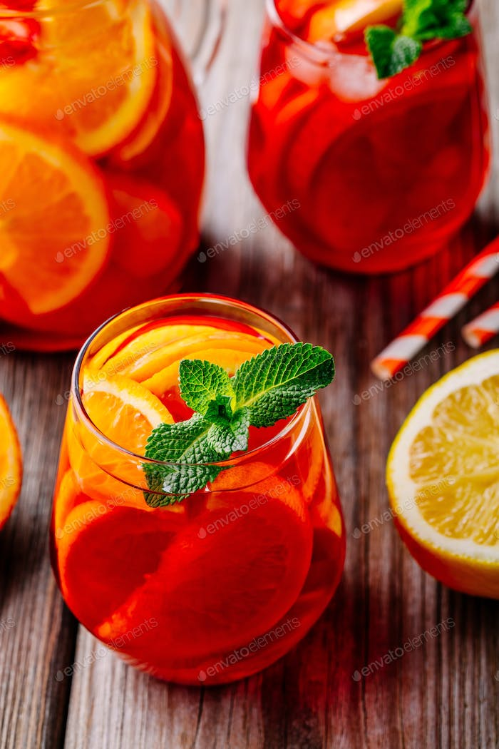 Homemade red wine sangria with orange, apple and ice in glass closeup on wooden background