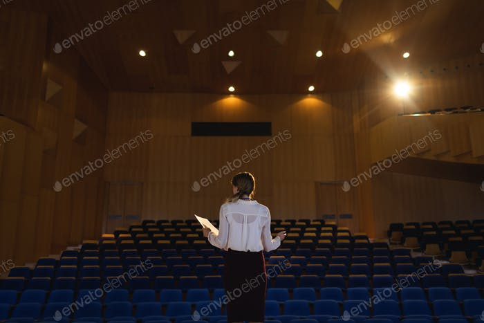 Beautiful businesswoman practicing and learning script while standing in the auditorium